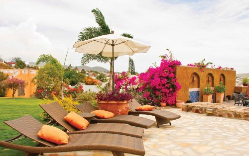 Brown wicker chaise lounges on a stone patio with orange cushions